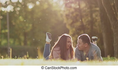 Romantic couple on a green glade in summer. They lie on the stomach, legs up. They look at each other touchingly. They play. Happy together in the rays of sunlight.