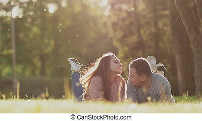 Romantic couple on a green glade in summer. They lie on their stomachs with their feet up. Happy together in the rays of sunlight.