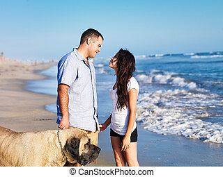 romantic couple on the beach with pet dog.