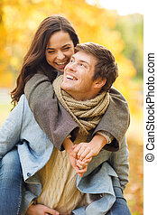 romantic couple playing in the autumn park - holidays, love,...