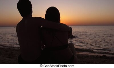 Romantic couple relaxing enjoying on beach looking at sunset