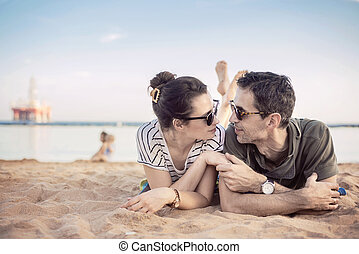 Romantic couple relaxing on a beach - Romantic, young couple...