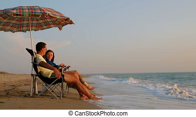Romantic Couple Relaxing On Folding Chairs Under Sunshades At Beach