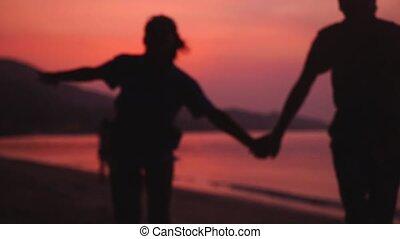 Romantic couple runs on the beach at amazing sunset holding...