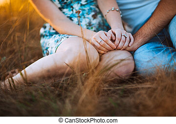 Romantic couple  sit on background summer meadow sunset