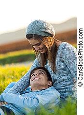 Romantic couple sitting in green field.