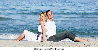 Romantic couple sitting on the sand