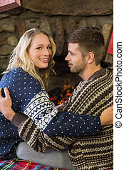 Romantic couple smiling in front of fireplace