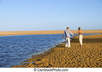 Romantic couple strolling along the waters edge