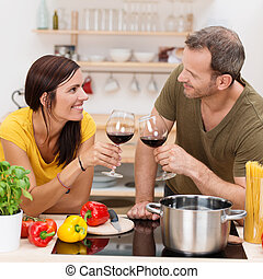 Romantic couple toasting each other in the kitchen