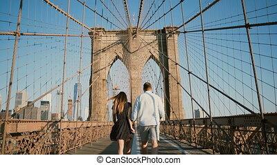 Romantic couple walk along Brooklyn Bridge NYC, hold hands...