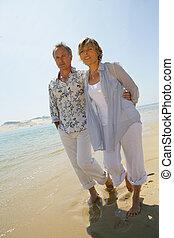 Romantic couple walking barefoot along a beach