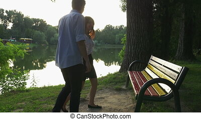 Romantic couple walking in the park and sitting on a bench
