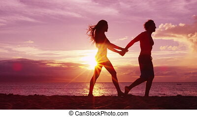 Romantic couple walking on beach holding hands at sunset with beautiful colors