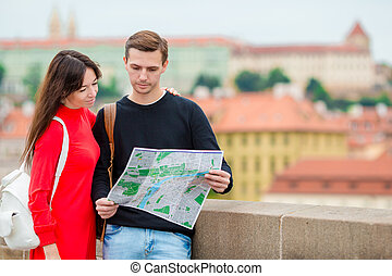 Romantic couple walking together in Europe. Happy lovers enjoying cityscape with famous landmarks. Stylish urban young man and woman with backpacks on travel in Prague