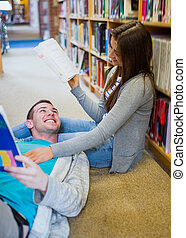 Romantic couple with books at the library aisle