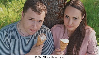 Romantic couple with ice cream at amusement park.