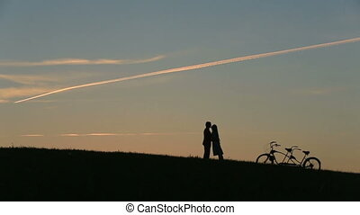 Romantic Couple with Tandem Bicycle Kissing While Sunset. Summer Nature Background with Beautiful Clouds in the Sky Close Up.