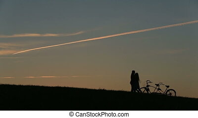 Romantic Couple with Tandem Bicycle Hugging While Sunset. Summer Nature Background with Beautiful Clouds in the Sky Close Up.