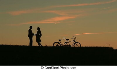 Romantic Couple with Tandem Bicycles Softly Kissing While Sunset. Summer Nature Background with Beautiful Clouds in the Sky Close Up