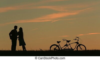 Romantic Couple with Tandem Bicycles Softly Kissing And...