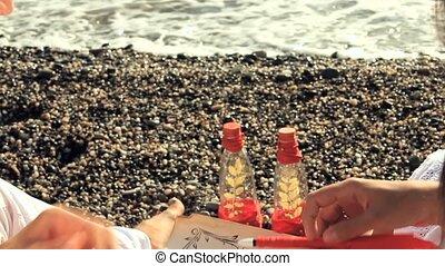 Romantic Couple Writing a Love Message Sitting on the Beach