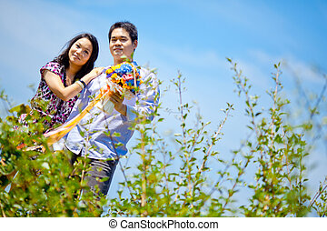 romantic couples standing outdoors with flowers bouquet