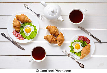 Romantic creative breakfast for two with heart shaped eggs, salad, croissants and black tea on white wooden table background. Food concept of love.