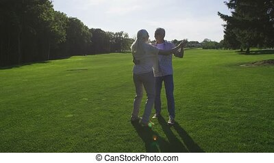 Romantic dance of senior wife and husband in park