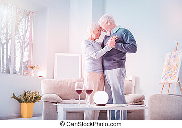 Couple of retired man and woman having extremely romantic date at home