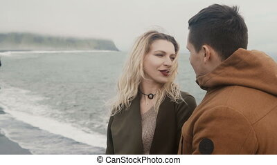Romantic date of young loving couple on black beach, near...