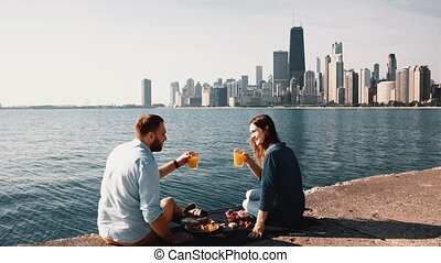 Romantic date on the shore of Michigan lake in Chicago, America. Beautiful couple enjoying a picnic together.