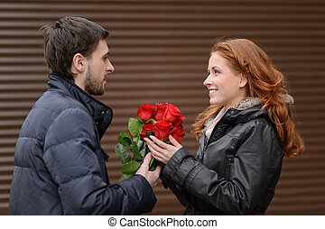 Romantic date. Young man presenting a bunch of red roses to his cute girlfriend