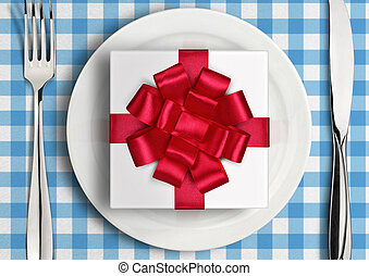 Romantic dinner concept, gift with ribbon on plate. Top view