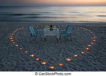 romantic dinner on the sea beach with candle heart