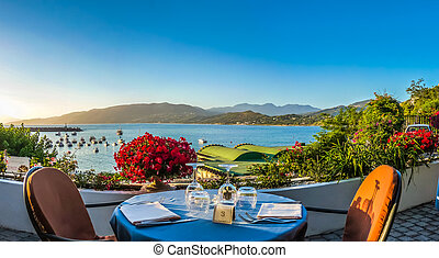 Romantic dinner place with idyllic view of coastscape at sunset