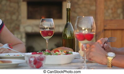 Romantic dinner with wine in the backyard beside stone fireplace close-up