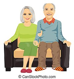 Romantic elderly couple sitting close together on a sofa isolated on white background