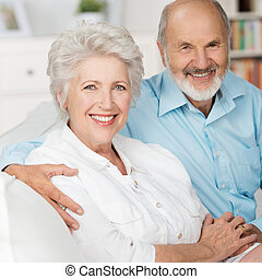 Romantic elderly couple sitting close together on a sofa in...