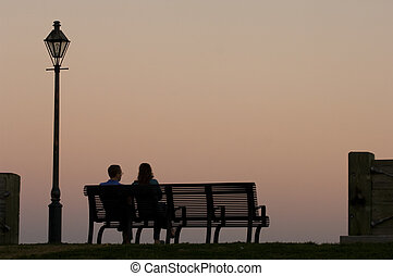 Romantic Evening - Couple sitting on the bench watching...