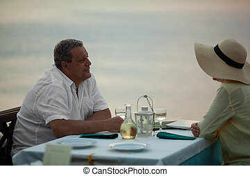 Romantic evening for mature couple in the seafront restaurant