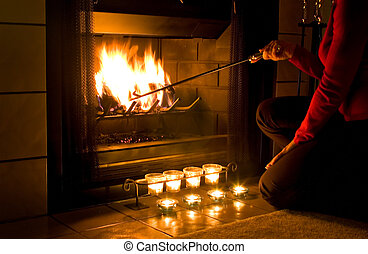 Romantic fireplace - Woman in red sweater stoking a fire in...