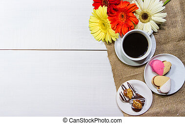 romantic flowers with coffee and sweet treats on the table