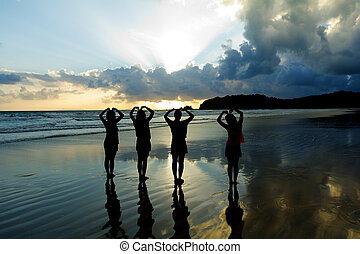 Romantic four young woman couple making heart shape with arms on beach at sunset  beautiful sky.