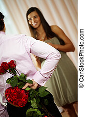 Romantic gift - A young man holding bouquet of roses and box...