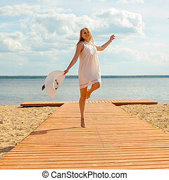 Romantic girl in a white dress with a white hat turned to the long-tailed wooden pier on the beach. The concept of joy and happiness
