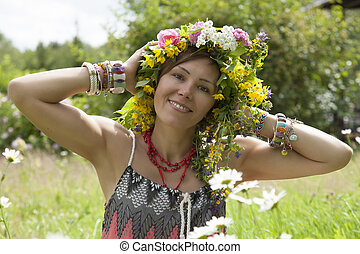 Romantic girl in a wreath of wild flowers