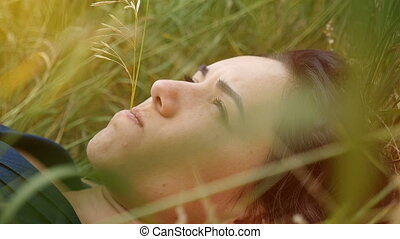Romantic girl lies on a green lawn on a sunny day in summer in slow motion
