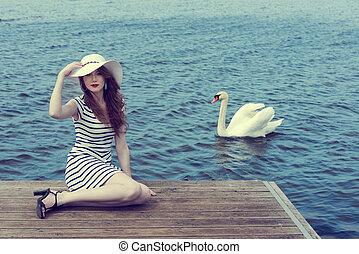 romantic girl near a swan on lake