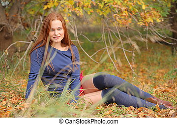 romantic girl sitting in autumn leaves
